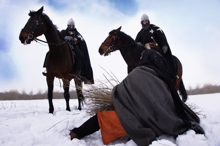 road warrior: Scared peasant with a firewood bundle and riding knights Hospitallers Stock Photo