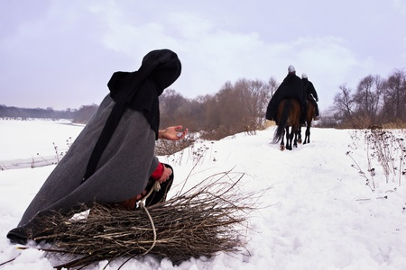 Medieval peasant with a firewood bundle and riding knights Hospitallers photo