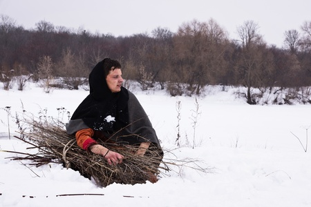Medieval peasant with a bundle of firewood sitting in the snow