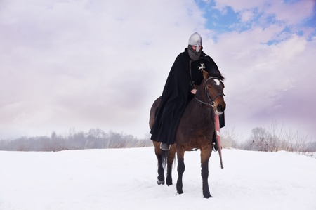hauberk: Medieval knight of St. John (Hospitallers) on a bay horses Stock Photo
