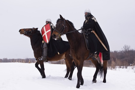 road warrior: Medieval knights of St. John (Hospitallers) on a bay horses Stock Photo