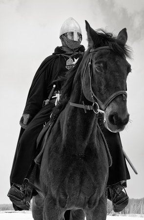 road warrior: Medieval knight of St. John (Hospitallers) on a bay horse Stock Photo