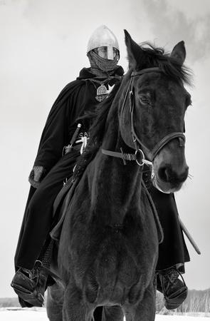 Middeleeuwse ridder van St. John (hospitaalridders) aan een baai paard Stockfoto