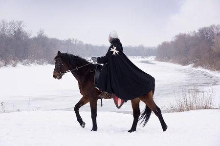 Medieval knight of St. John (Hospitallers) on a bay horse Stock Photo - 13452054
