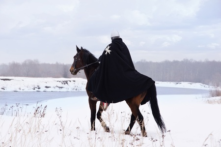 Medieval knight of St. John (Hospitallers) on a bay horse Stock Photo - 13452017