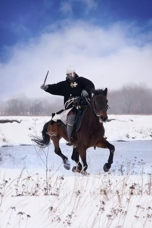 Middeleeuwse ridder van St. John (hospitaalridders) rijden op een baai paard Stockfoto