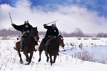 Medieval knights of St. John (Hospitallers) riding on a bay horses   Stock Photo