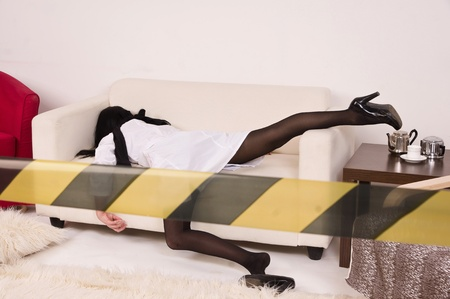 Crime scene imitation. Lifeless nurse lying on the sofa photo