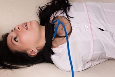 Crime scene imitation. Strangled nurse lying on the floor Stock Photo - 13761596