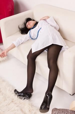 Crime scene imitation. Lifeless nurse lying on the sofa photo