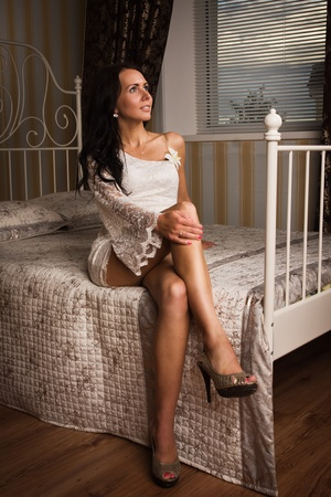 Attractive brunette sitting on the bed  in a boudoir photo