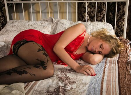 Sexual blonde in red sleeping in a boudoir Stock Photo - 14430653