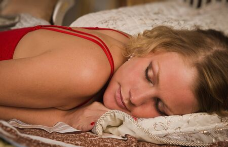 Sexual blonde in red sleeping in a boudoir photo