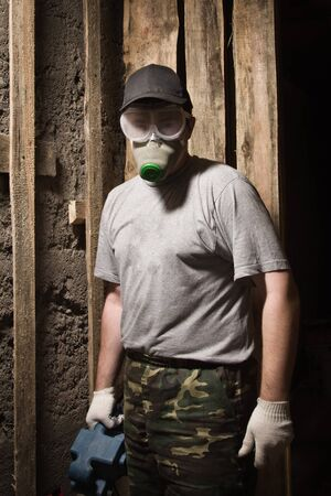 Builder in a respirator and goggles with sander photo