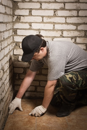 Builder setting ceramic tile on cement floor Stock Photo - 14430685