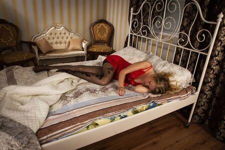 boudoir: Sexual blonde in red sleeping in a boudoir