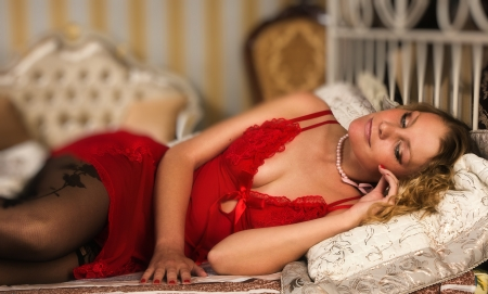 Sexual blonde lying on the bed  in a boudoir photo