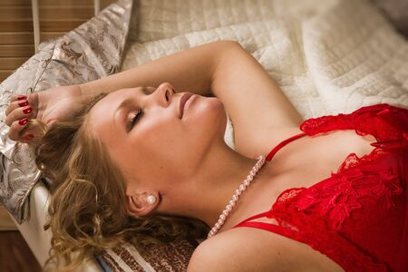 Sexual blonde in red sleeping in a boudoir Stock Photo - 14484366