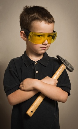 Little boy in goggles with a hammer photo