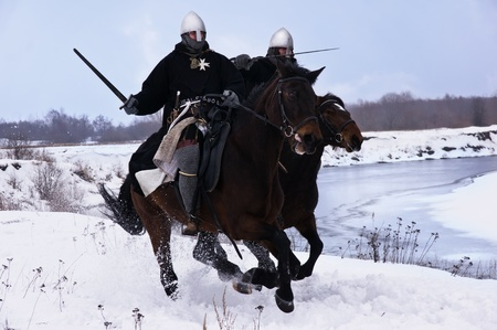 Medieval knights of St. John (Hospitallers) riding on a bay horses photo