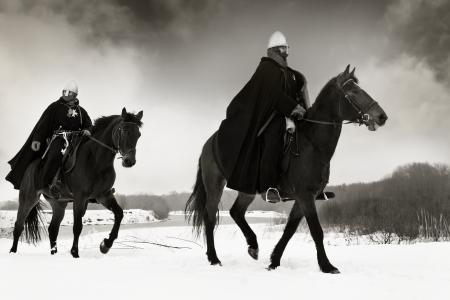 Middeleeuwse ridders van St. John (hospitaalridders) rijden op een baai paarden