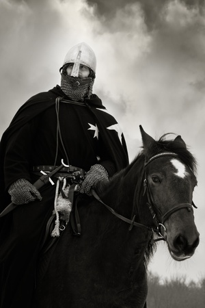 Medieval knight of St. John (Hospitaller) riding on a bay horse photo
