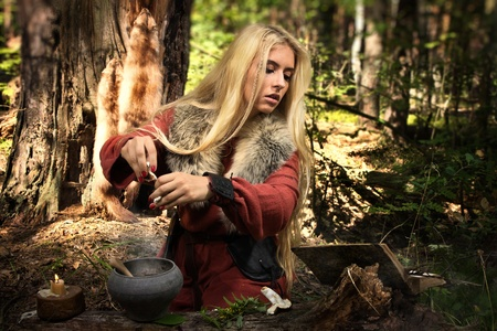 cosplay: Scandinavian witch pythoness cooking potion in a dark forest
