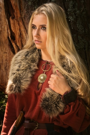 Scandinavian girl with runic signs on a forest background Archivio Fotografico