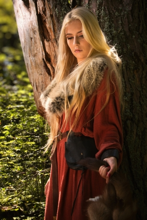 medieval dress: Scandinavian girl with runic signs holding a fur skins