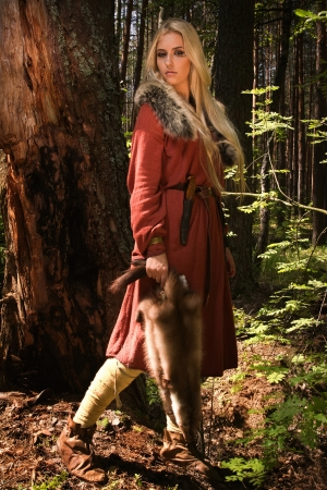 Scandinavian girl with runic signs holding a fur skins photo