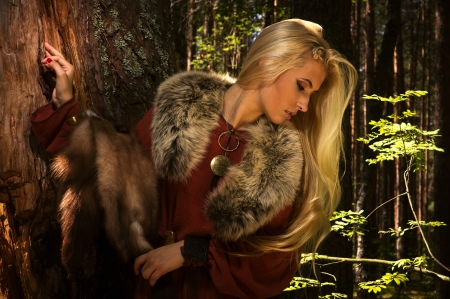 historical clothing: Scandinavian girl with fur skins on a forest background
