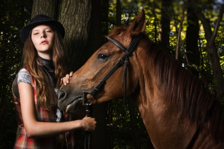 Young cowgirl in hat with bay horse photo