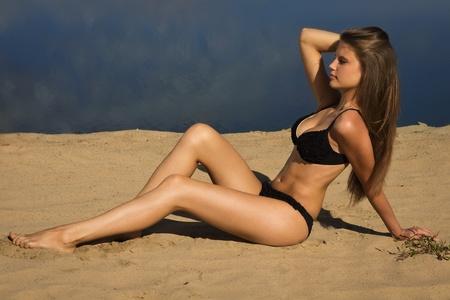 Attractive girl in a bikini on a sandy beach photo