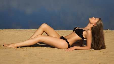 Attractive girl in a bikini on a sandy beach
