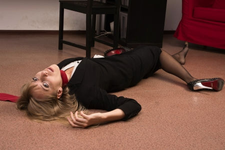 homicide: Crime scene imitation. Lifeless business woman lying on the floor
