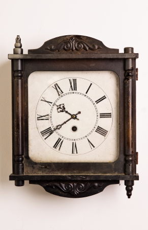 Old wooden grandfather clock hanging on a wall