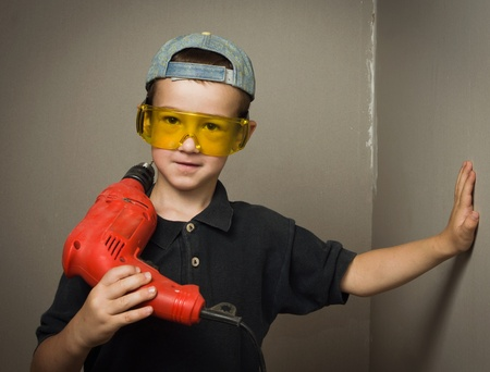 Little boy in goggles with electric drill photo