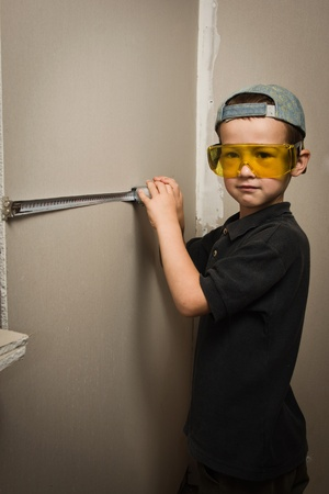 Little boy in goggles with a tape measure photo