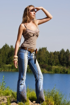 Attractive cowgirl in jeans stands on the bank of forest river photo