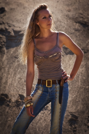 Attractive cowgirl in jeans on a sandy background photo