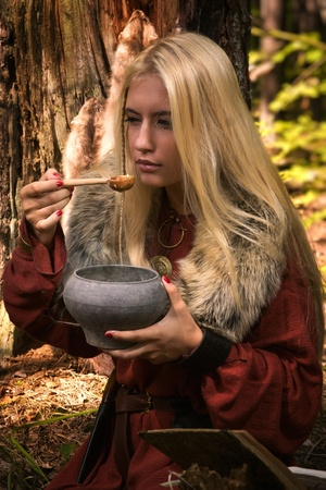 Scandinavian witch pythoness cooking potion in a dark forest photo