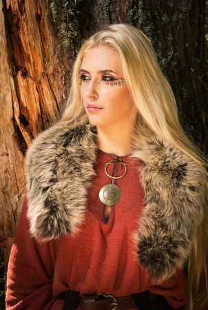 runes: Scandinavian girl with runic signs on a forest background Stock Photo