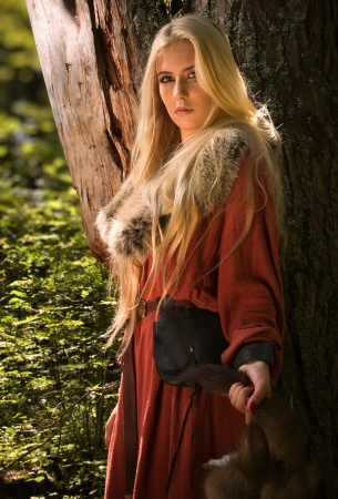 historical clothing: Scandinavian girl with runic signs holding a fur skins