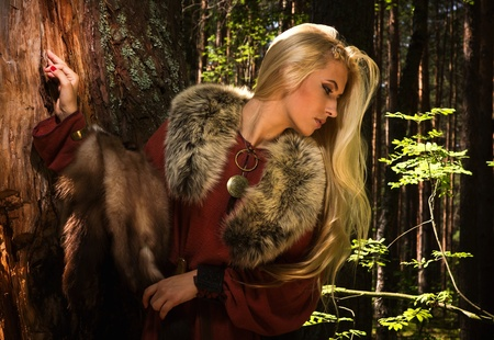 Scandinavian girl with fur skins on a forest background photo