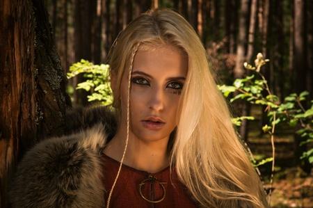 medieval dress: Chica escandinava con signos r�nicos en un fondo forestal
