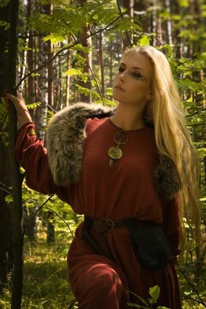 abito medievale: Ragazza scandinava con segni runici su uno sfondo foresta Archivio Fotografico