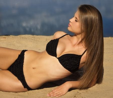 badpak: Aantrekkelijk meisje in een bikini ontspannen op een zandstrand