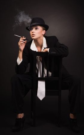 Vintage adult woman smoking cigarette in bar
