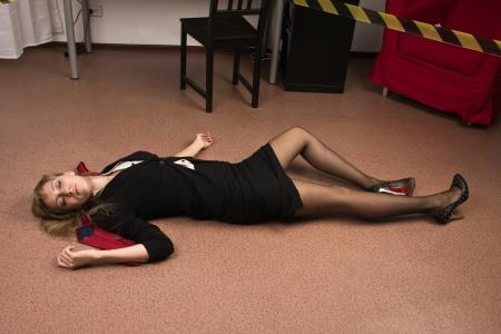 Crime scene imitation. Lifeless business woman lying on the floor