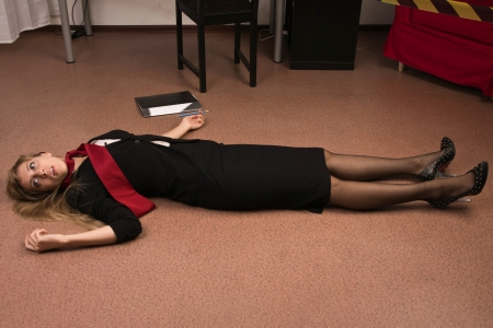 scene of a crime: Crime scene imitation. Lifeless business woman lying on the floor